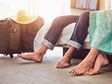 A close-up of a husband and wife's bare feet on the floor of their hotel room.